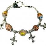 Berlockarmband med sirliga kors och handgjorda indiska glaspärlor